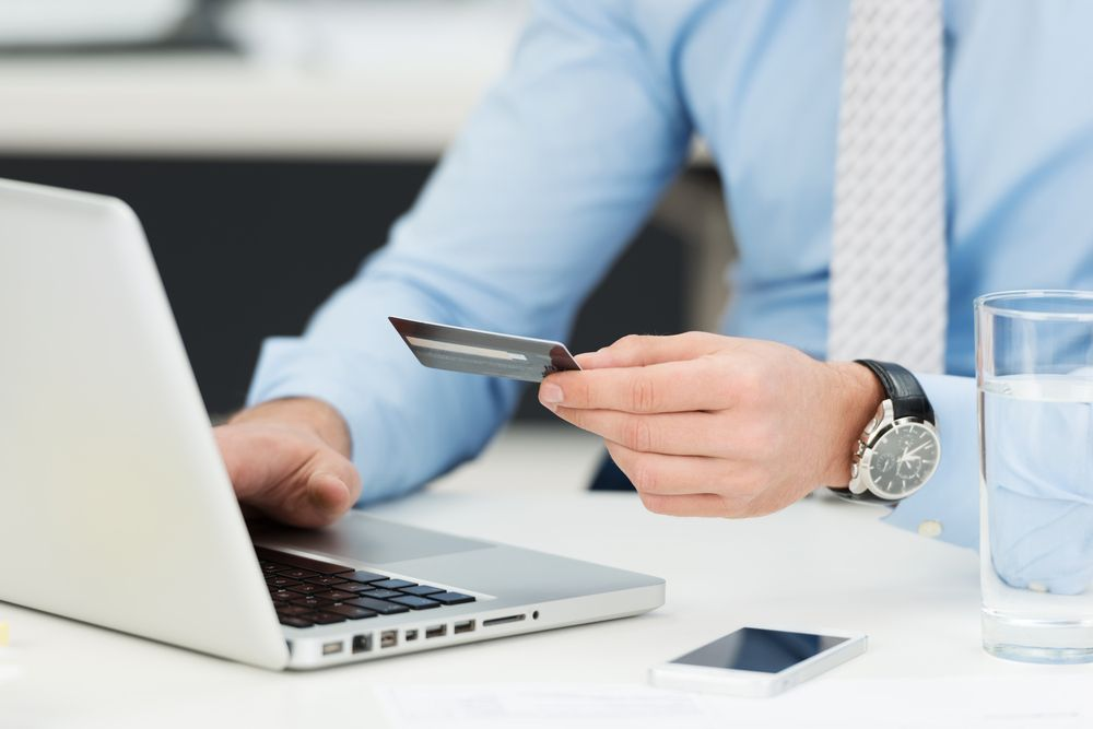 Online payment with laptop, close up with credit card in hands