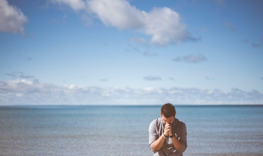 Man Giving Thanks in Prayer at a Beach