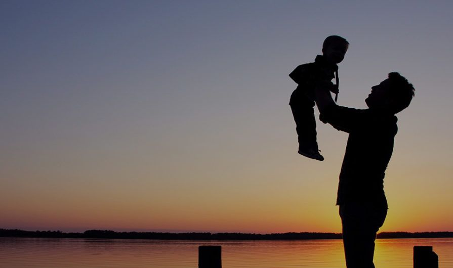 Silhouette of Man Holding Boy at Sunset