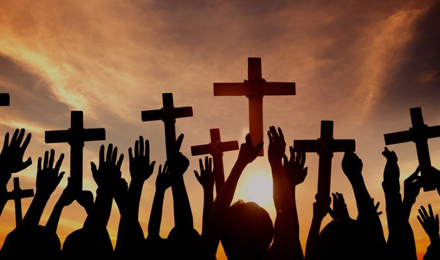 Silhouettes of People Holding Up Crosses at Sunset