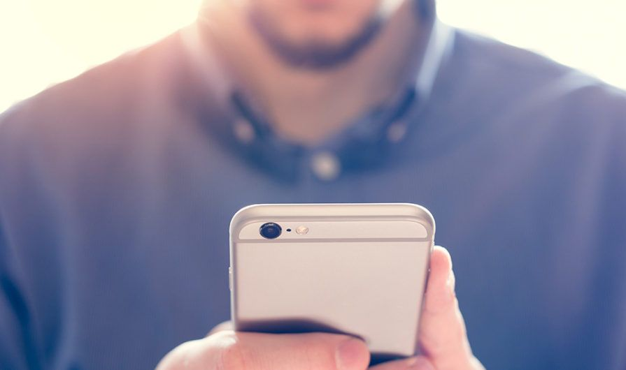 Man looking at a mobile giving app on his phone