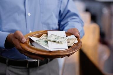 Man holding church offering plate for tithes
